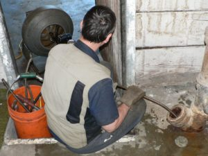 clearing a clog in a pipe - plumbing services